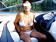 Sexy wife gives a striptease inside of speed boat on lake